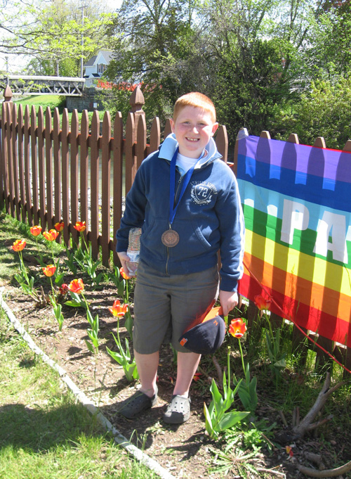 Evan Cummings, age 8, is the youngest volunteer at the Bicentennial Peace Garden in Batavia.