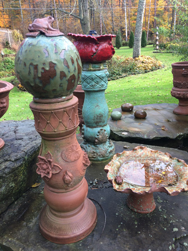 Garden sculptures with ornate finials, and a low birdbath with an everpresent toad.